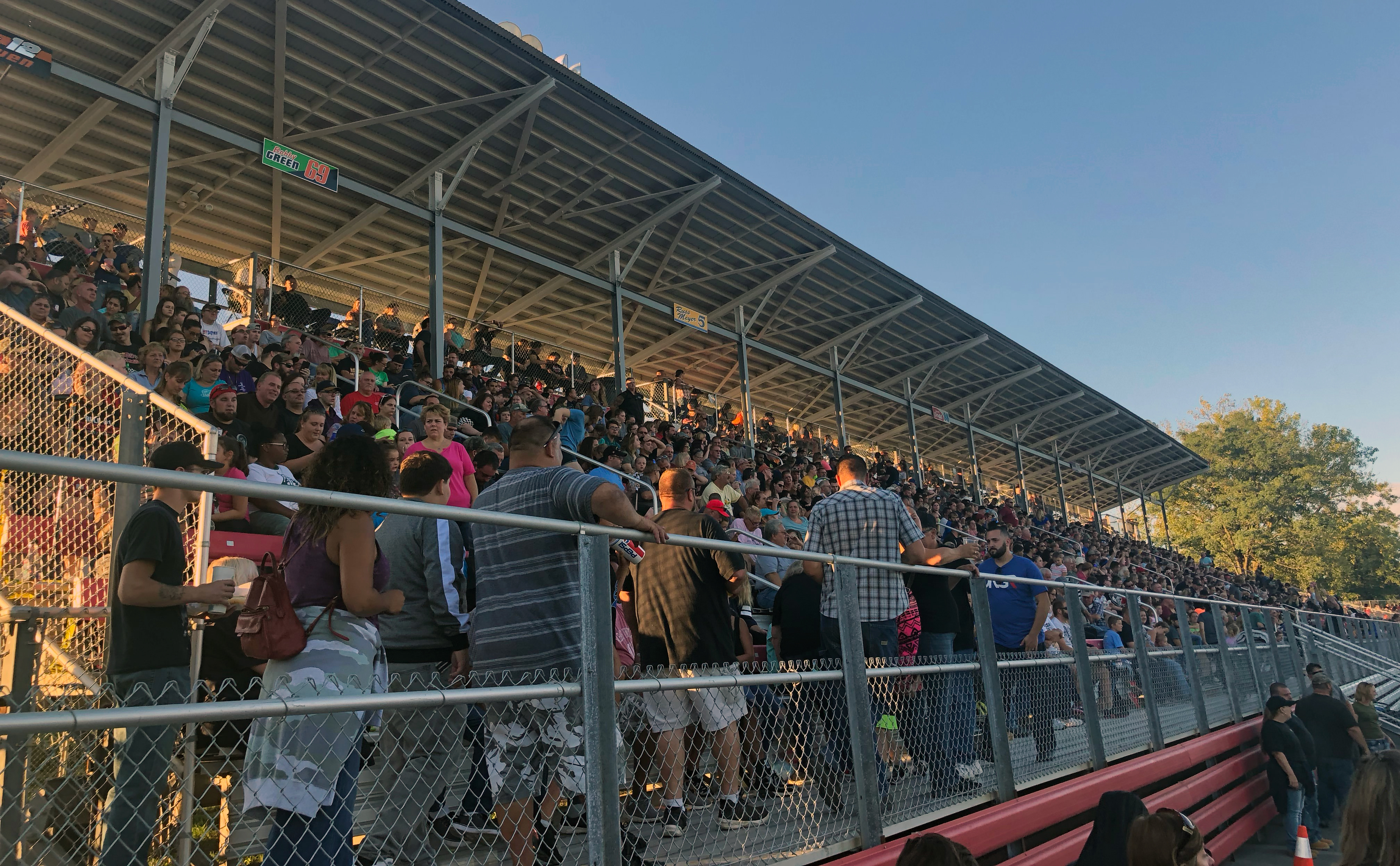 Fans load into the half covered grandstand on the Speedway's front stretch.